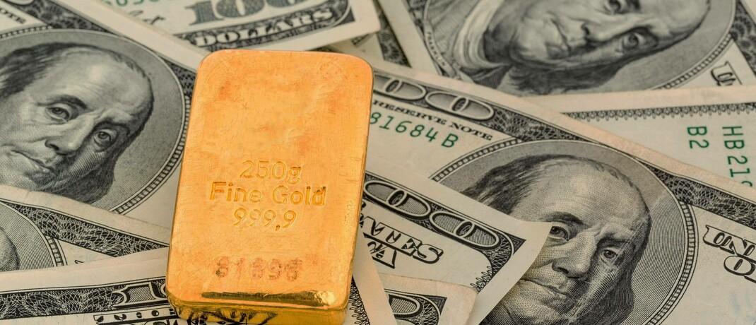 Goldbarren auf gesetzlichem Zahlungsmittel: Trotz der positiven Entwicklung an den Aktien- und Anleihemärkten erweist sich der Goldpreis als Alternative zum selbst geschaffenen und negativ verzinsten Geld der Notenbanken stabil.
