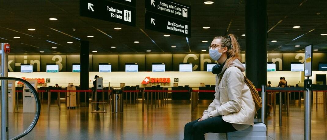"""Flugreisende mit Maske: Der neue Vertragsbestandteil """"Covid Protect"""" beinhaltet den Service einer Notfall-Hotline und einer App mit ärztlicher Teleberatung und medizinischer Assistenz während des Urlaubs."""