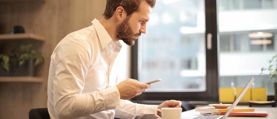 Mann mit Handy und Laptop: Der Aktiencrash mitsamt Corona-Krise ging im März durch alle Medien.