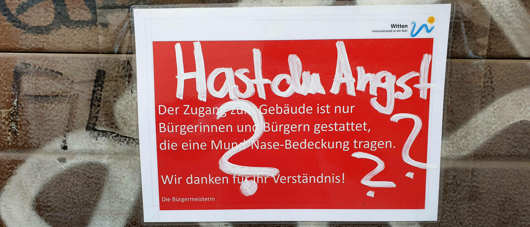 Graffiti und Hinweisschild zur Maskenpflicht an der Wand eines Amtsgebäudes in Witten.|© Imago / Blickwinkel