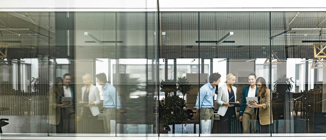 Eine Besprechung hinter den Glasfenstern eines Bürogebäudes: Büros bleiben für den Austausch und die persönlichen Kontakte relevant. |© imago images / Westend61