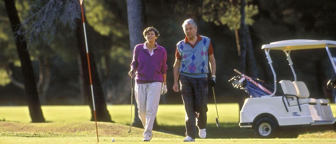 Seniorenpaar mit Golf-Caddy. Diesen Sport können sich Beamte wegen höherer Bezuge in der Regel eher leisten als Rentner.