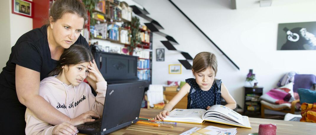 Mutter beim Homeschooling mit ihrem Töchtern. Einer Aon-Umfrage zufolge sieht rund jede dritte zweifache Mutter Partner und Familie als Haupteinnahmequelle im Alter.