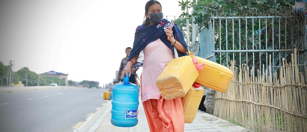Eine Frau in Nepal trägt Trinkwasser: Die Wasserversorgung ist ein wichtiges Thema von Impact Investments.|© imago images / Pacific Press Agency / Dipendra Dhungana