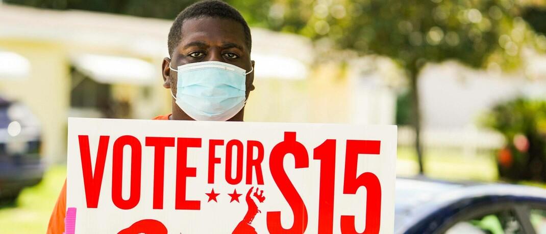 Der 19-jährige US-Amerikaner Trayvonne Williams mit Plakat: Er hofft, dass der Mindestlohn demnächst auf 15 Dollar die Stunde steigt.|© imago images / ZUMA Wire / Martha Asencio Rhine