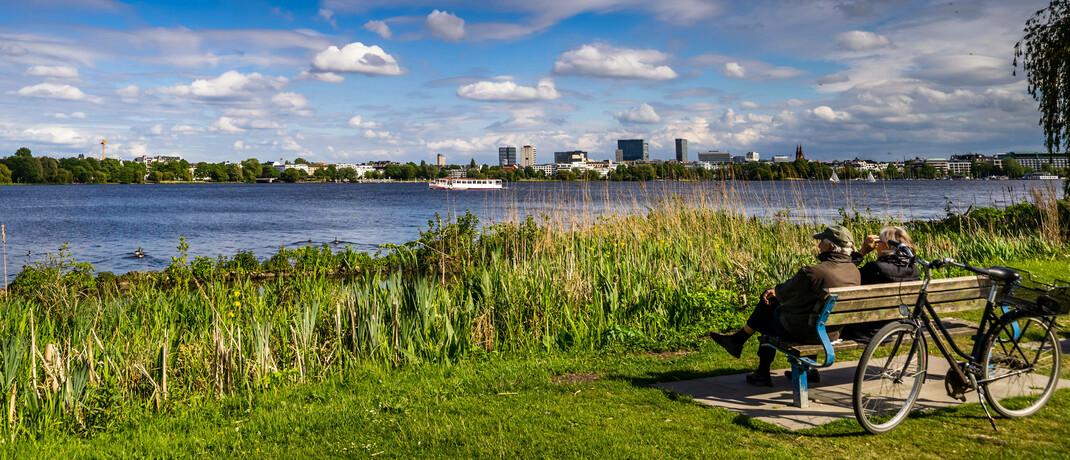Senioren auf einer Parkbank an der Alster in Hamburg: Je nach Region bleibt den Rentnern unterschiedlich viel Geld zum Leben.|© imago images / Hoch Zwei Stock/Angerer