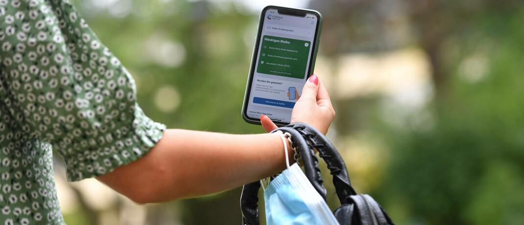 Frau betrachtet Corona-Warn-App auf ihrem Smartphone: Jeder zweite Deutsche hält Apps wie diese laut einer Canada Life-Umfrage für sinnvoll © Imago / Sven Simon