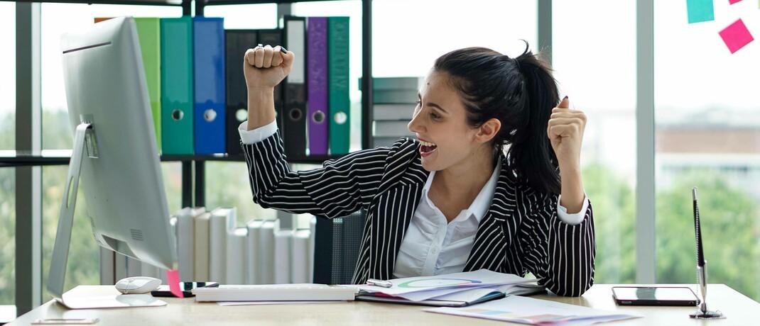 Junge Frau in Siegerpose an ihrem Schreibtisch