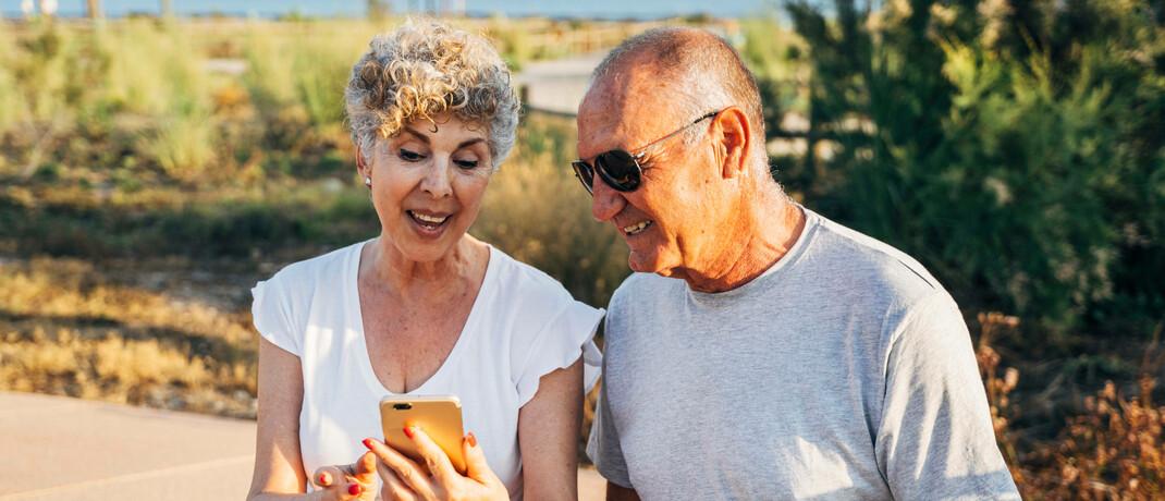 Seniorenpaar im Urlaub mit Smartphone
