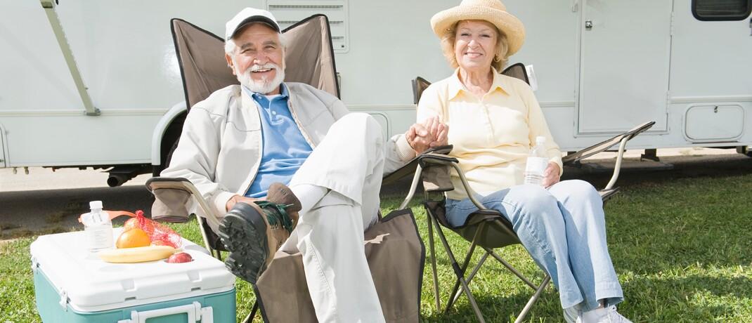 Rentnerpaar vor seinem Wohnmobil