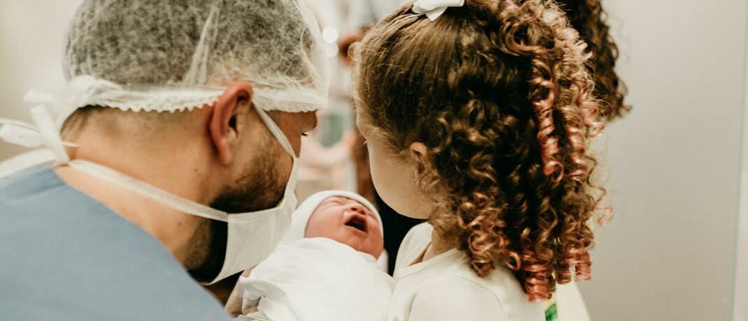 Neugeborenes mit Vater und Schwester
