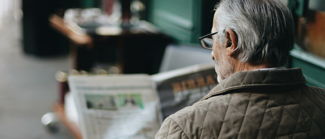 Älterer Mann liest Zeitung in einem Café