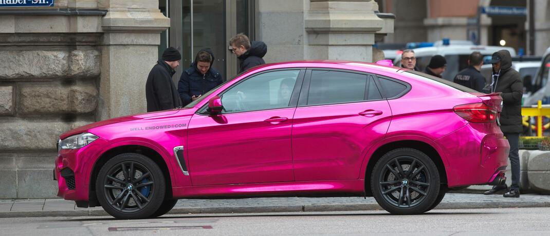 Ein SUV mit chrom-pinkfarbener Lackierung vom Typ BMW X6