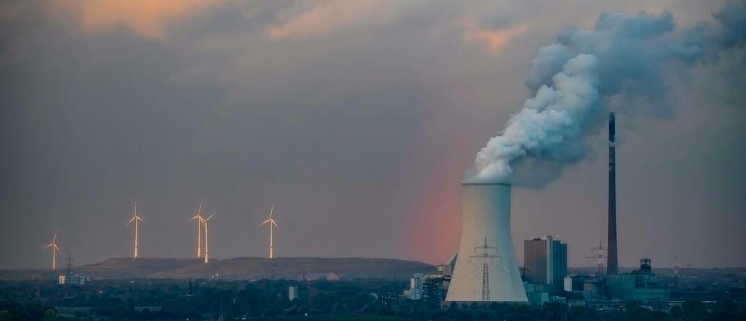 Kühlturm eines Kohlekraftwerks, im Hintergrund Windkraftanlagen