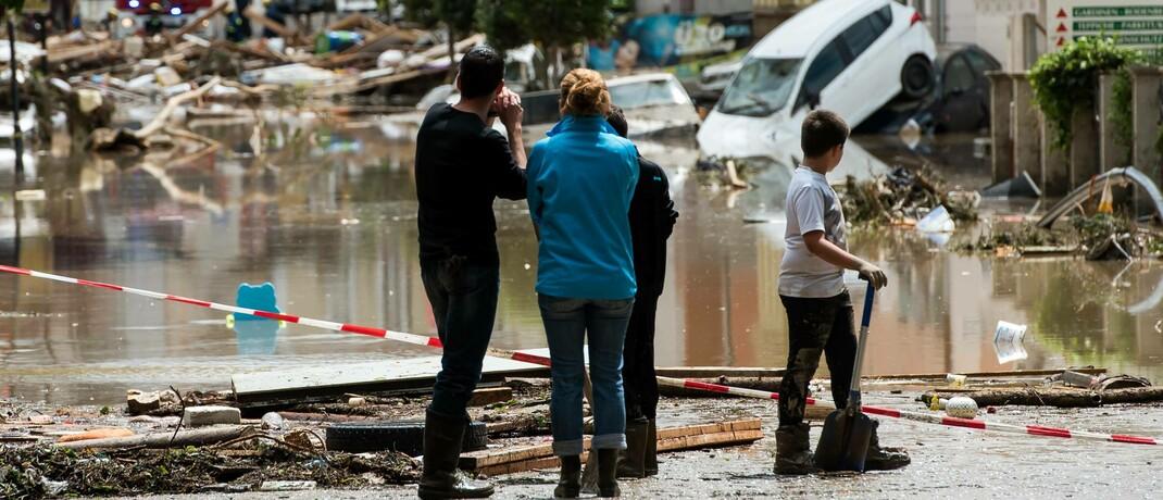 Helfer blicken in Simbach am Inn auf eine überflutete Straße