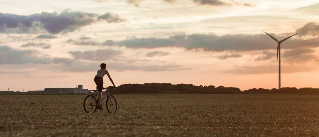 Radfahrer vor Windkraftanlage