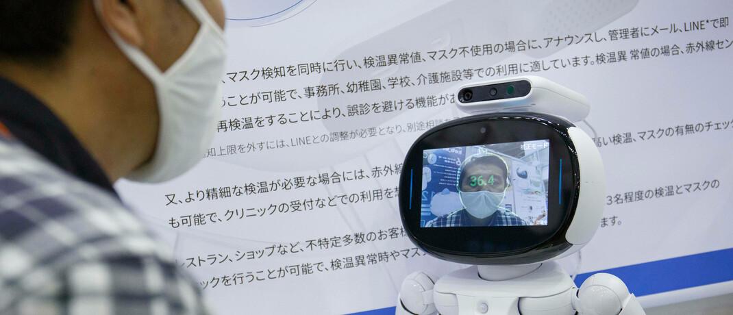 Roboter misst Temperatur bei Messebesucher in Japan