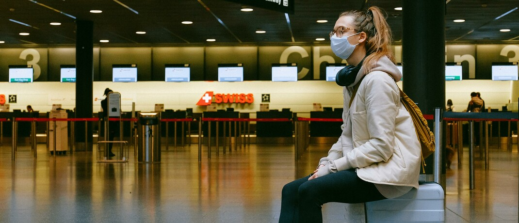 Frau mit Mundschutz im menschenleeren Flughafengebäude