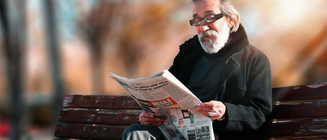 Älterer Mann liest Zeitung auf einer Parkbank