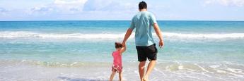Vater mit Tochter am Strand: Banker haben mehr Urlaub als Angestellte in anderen Branchen