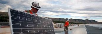 Arbeiter bei der Montage eines Photovoltaik-Moduls