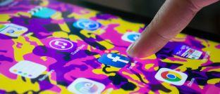 """Ein Nutzer tippt auf das Logo der Facebook-App auf seinem Smartphone-Display: """"Viele Leute nutzen Facebook häufiger als sie sich die Zähne putzen"""", kommentiert Morgan-Stanley-Manager Kristian Heugh den Medienkonsum vieler Menschen."""