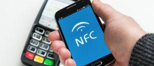 """Mobile Payment per """"Near Field Communication"""": Indem Kunden ein NFC-fähiges mobiles Endgerät an ein Kassenterminal halten, können sie statt mit Bargeld oder EC-Karte auch mit dem Smartphone bezahlen."""