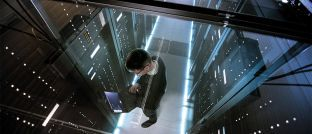 Ein IT-Techniker arbeitet mit Laptop im Rechenzentrum: In einer Minute werden weltweit 150 Millionen E-Mails verschickt.