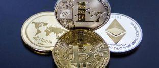 Münzen der Kryptowährungen Ripple, Litecoin, Bitcoin und Ethereum (v.l.): Auch der Finanzvertrieb kann vom Trend zu Investments in Kryptowährungen profitieren.