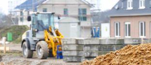 Bagger in einer Neubausiedlung: Wer Grundstückskauf und Bauauftrag getrennt voneinander abwickelt, kann wertvolles Eigenkapital sparen.