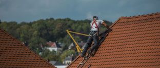 Ein Dachdecker verlegt Dachziegeln auf einem Hausdach: Für Menschen mit gefährlichen Berufen, wie eben Dachdecker, ist eine Berufsunfähigkeitsversicherung oft unbezahlbar.