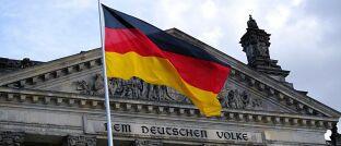 Bundesflagge vor dem Reichstagsgebäude in Berlin, dem Sitz des Deutschen Bundestages.