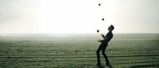 Jongleur beim Üben auf einem Feld: Auch Geraldine Sundstrom hält gleichzeitig mehrere Bälle in der Luft, indem sie auf verschiedene Anlageklassen setzt.