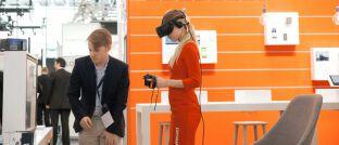 Eine Frau testet das Bezahlen per Virtual-Reality-Brille an einem Wirecard-Messestand: Die Aktie des jüngsten Dax-Unternehmens mit Sitz in Aschheim bei München verzeichnete in den vergangenen zwölf Monaten heftige Ausschläge. Der Kurs schwankte zwischen 199 und 86 Euro.
