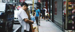 Mann mit seinem Mobiltelefon in China: Schwellenländer stehen in den Bereichen E-Commerce, digitaler Zahlungsverkehr, mobile Bankgeschäfte und Elektrofahrzeuge an der Innovationsspitze.