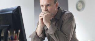 Berater vor einem Bildschirm. Viele Mitarbeiter der Bankenbranche sind mit ihren Arbeitsbedingungen nicht glücklich.