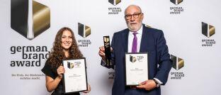 Jasmin Haj, Marketing & Vertrieb, und Walter Capellmann, Hauptbevollmächtigter der Dela Lebensversicherungen in Deutschland, nehmen die Preise entgegen.
