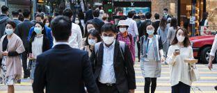 Passanten mit Atemmaske in Hongkong: Der Corona-Virus bremst die Weltwirtschaft aus.