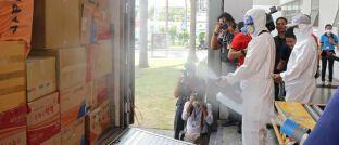 """Thailändische Post-Mitarbeiter desinfizieren Pakete, Pressevertreter schauen zu: Morningstar-Mann Ali Masarwah ärgert sich über """"alarmistische Berichterstattung"""" in Zusammenhang mit dem Coronavirus."""