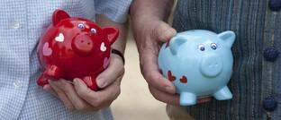 Paar mit Sparschweinen: Statt der Spardose wird zunehmend Geld in Fondssparplänen angelegt.