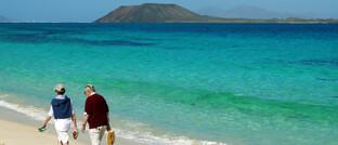 Rentner am Strand: Wer im Alter viel verreist, sollte eine Auslandsreisekrankenversicherung abschließen.