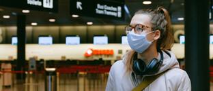 Frau mit Mundschutz: Der Kampf gegen das Coronavirus führt zu steigenden Kosten im Gesundheitssystem.
