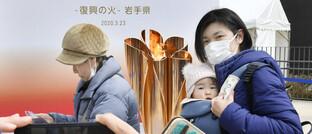Passanten in Japan vor der Olympischen Fackel: Auch Nippons Unternehmen leiden unter den Folgen der Corona-Pandemie