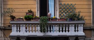Eine ältere Dame hört angesichts der Corona-Kontaktsperre Musik auf ihrem Balkon in Porta Genova: Das Corona-Virus sorgt für eine neue Form von gesellschaftlichem Zusammenhalt, und das nachhaltig, glaubt Matthias Horx.