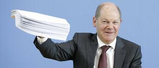 Finanzminister Olaf Scholz zeigt auf der Pressekonferenz den Aktenstapel, der die neuen Gesetze für das Hilfspaket enthält.