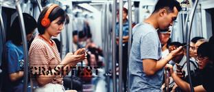 Handy-Nutzer in der U-Bahn von Peking: Nachrichten von Tencent, Einkaufen mit Alibaba