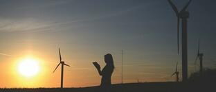 """Frau vor Windkraftanlagen: Neben Umweltfragen """"bedarf es auch der Berücksichtigung ethischer und sozialer Kriterien, der Mitarbeiterbelange und guter Governance, um einen wirklich nachhaltigen Ansatz zu schaffen"""", sagt Prismalife-Chef Holger Beitz."""