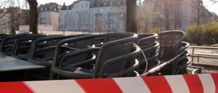 Mit Absperrband versperrter Außenbereich eines Cafés in München Schwabing: Hotels und Restaurants in Bayern, die eine Betriebsschließungsversicherung haben, bekommen bis zu 15 Prozent der vereinbarten Tagessätze erstattet.