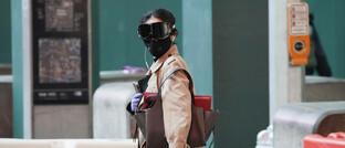Passantin mit Schutzkleidung: Die wirtschaftlichen Probleme durch die Corona-Pandemie will die Regierung mit weitreichenden Maßnahmen mildern
