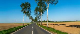 Landstraße und Windräder: Helvetia unterstützt als Investor unter anderem den Bau von Windkraftanlagen